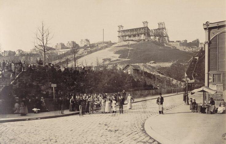 """Construction de l'église du Sacré-Cœur à Montmartre. Paris XVIIIe. 10 mars 1882. Photo : Louis-Émile Durandelle.  Au premier plan, le square Saint-Pierre (1877). À droite, la rue Ronsard et le marché de Montmartre (aujourd'hui dite la """"halle Saint-Pierre""""), marché public alimentaire de 284 places construit en 1867 et inauguré le 2 janvier 1868. En fer, 36 sur 82 m, toiture soutenue par 52 colonnes en fonte, 34 fenêtres de 3,5 m de haut. Construit et exploité en concession par la Compagnie…"""