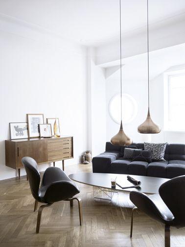 deco salon minimaliste pour une ambiance zen avec un mobilier vintage, canapé et fauteuil cuir noir, grandes suspensions en cuivre