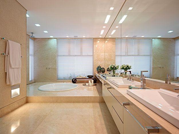 Banho do casal: conta com dois níveis e é revestido em mármore botticcino. A bancada se estende pelos níveis, separando as áreas da cubas e acessórios (Jomar Bragança/Divulgação)