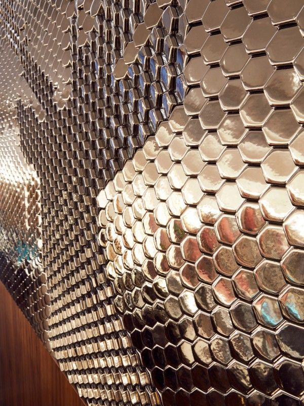 The reflective hexagonal ceramic tile created five stag silhouettes composed across an 11m long reception wall at the Sheraton Hotel in Edinburgh - by Giles Miller Studio