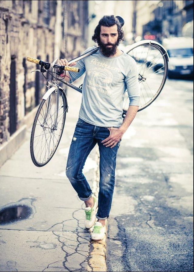 Hipster in street outfit with skinny jeans, grey shirt, trainers, and bike.