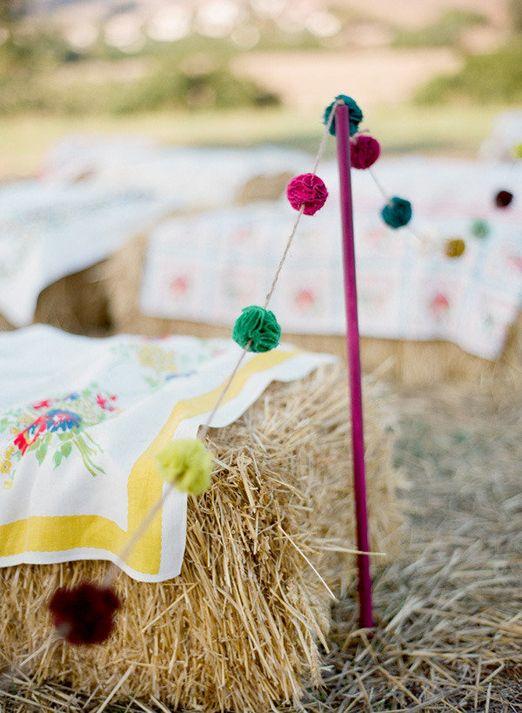 Colourful pom pom garland for an outdoor wedding aisle