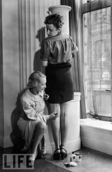 A representative of Max Factor paints cream stockings onto a woman's leg as a solution to the unavailability of nylon during World War ll; May 25, 1940.