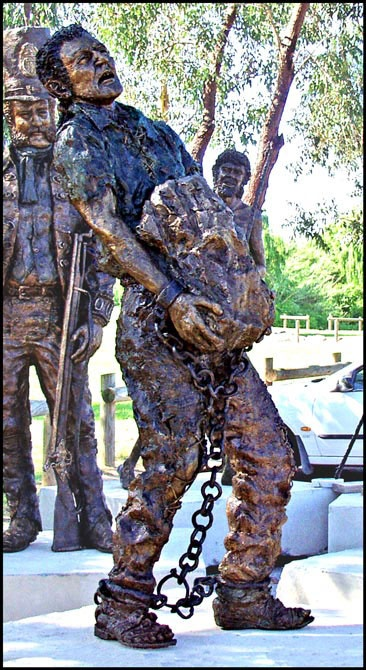A statue representing the manual labour of carrying and transporting hefty rocks. The statue has its ankles and wrists in shackles.