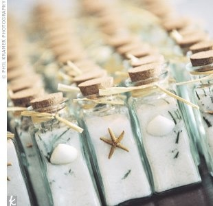 beach favors glass bottles filled with white sand, starfish and shells.