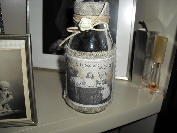 oud melkflesje opgepimpt met jute en een plaatje