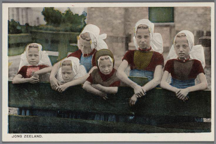 Zes meisjes in Walcherse streekdracht. Het vierde meisje van links draagt nog een gehaakt mutsje over haar ondermuts met oorijzer. na 1905 #Zeeland #Walcheren