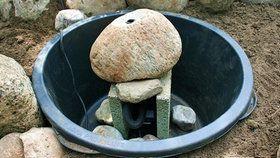 Maurerkübel mit Steinen und Brunnenpumpe