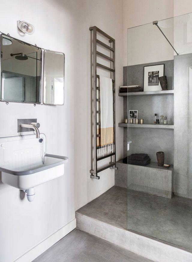 Une chouette salle de bains teintée de béton ciré gris et d'objets déco chinés.