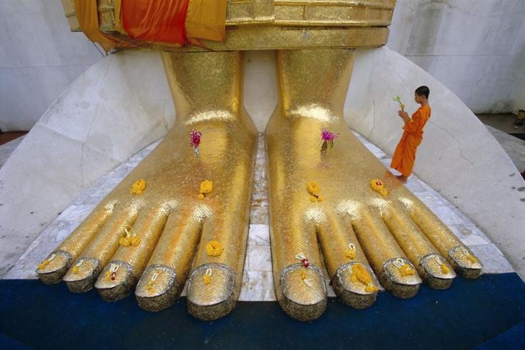 Un monje a los pies de la estatua gigante de buda en el templo de Wat Intharawihan, en Bangkok. / GAVIN HELLIER