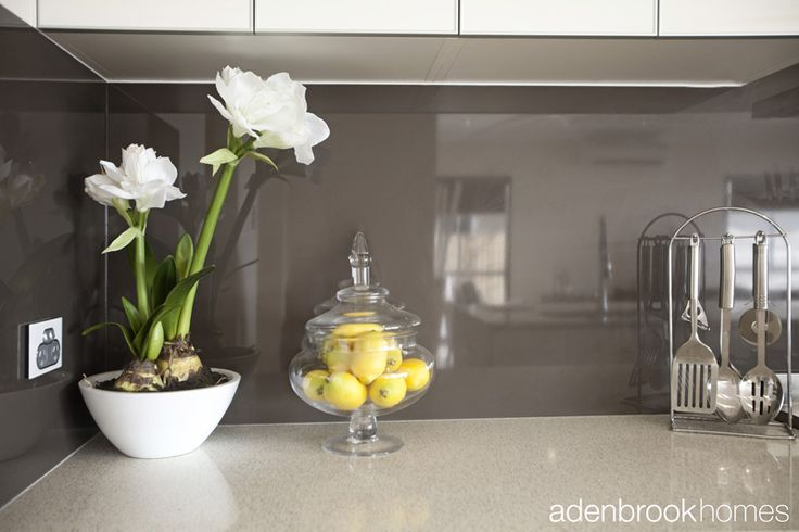 Classy yet contemporary glass splashback. White bench tops and dark Laminate cupboards
