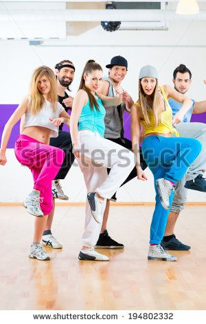 Young men and women dancing zumba modern group choreography in dance school - stock photo
