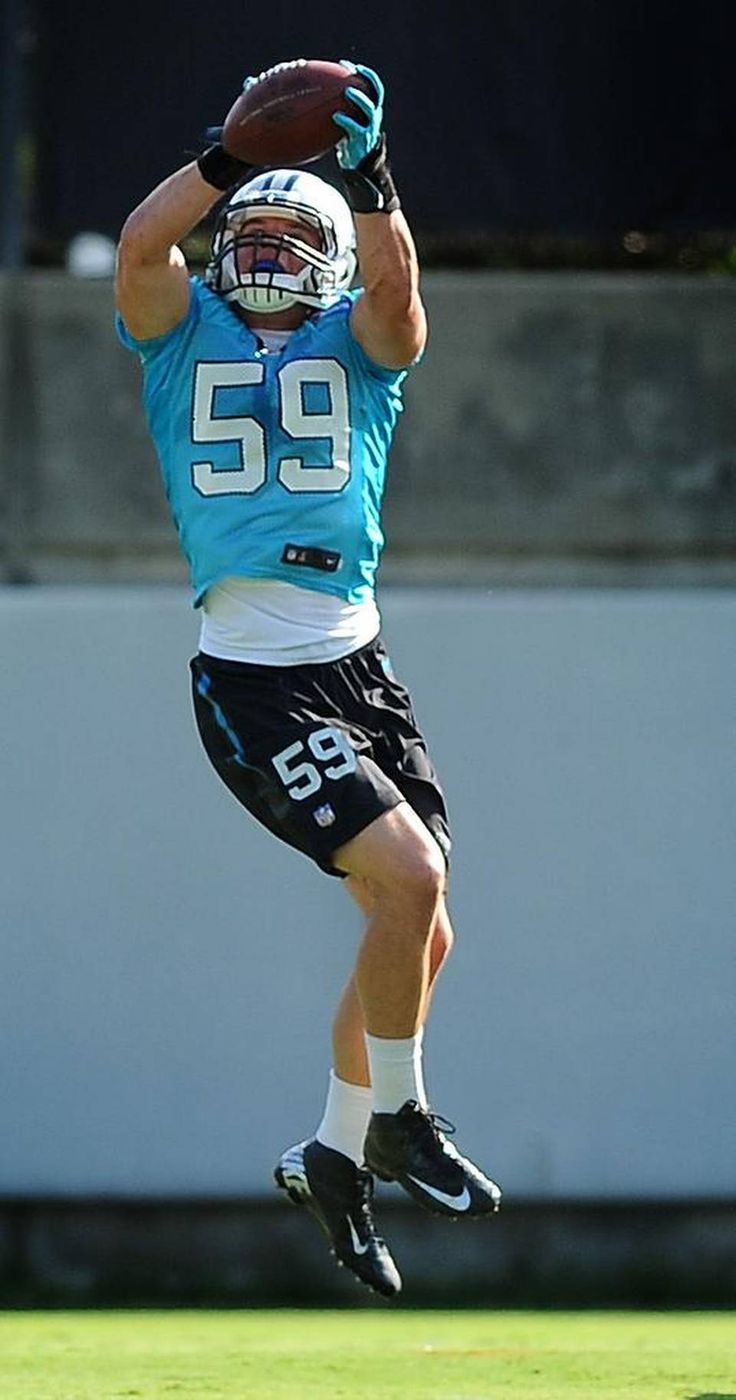 Carolina Panthers linebacker Luke Kuechly leaps into the air to catch a ball during practice on Wednesday, August 26, 2015.
