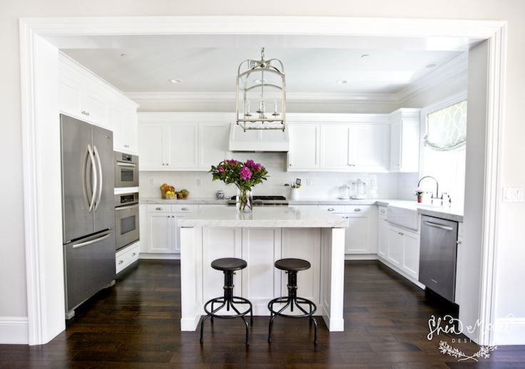 Stunning kitchen with Visual Comfort Lighting Large Arch Top Lantern in Polished Nickel over square kitchen island topped with carrera marble countertop lined with industrial barstools.