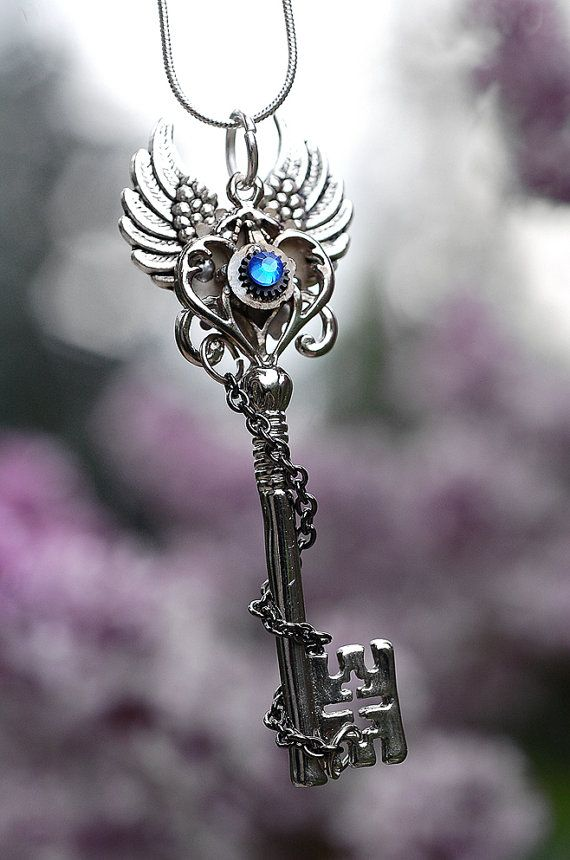 Large decoravtive key with jewelry pieces attached.