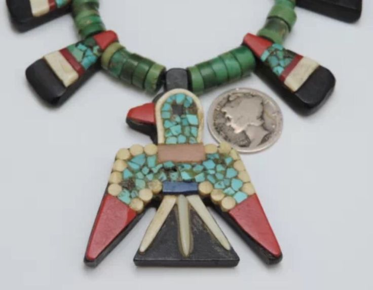 Santo Domingo Pueblo, depression era, 'battery bird', recycled material, thunderbird necklace. These were made by Native American artists during the Great Depression as inexpensive souvenir items, made of recycled plastics, broken records, toothbrush handles, the black vulcanite casings to early car batteries, bone, and small amounts of turquoise. The beads they were typically strung with were made of a dense talc-like material.