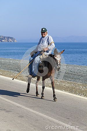 SAMOTHRACE, GREECE - AUGUST 14: An old man riding his mule somewhere in Lakkoma on the way to work on August 14, 2012 in Samothrace, Greece