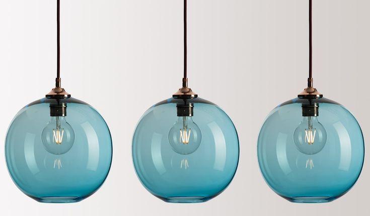 Three handblown round glass pendants in Copper Blue glass with copper metalwork