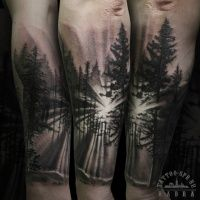 Spectacular black and white forest sunrise tattoo on forearm