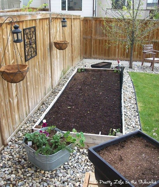 planting bed surrounded by gravel. I LOVE this idea for if you have a small-ish backyard in a condo. I would make the iron decor in the center a wall fountain, and instead of planting flowers there would be veggies. :) But I LOVE the concept!