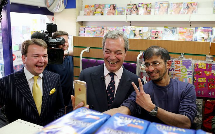 UKIP party leader Nigel Farage (2nd L) poses for a photo with a member of the public as he visits shops on a campaign visit to the high street on April 13, 2015 in South Okendon