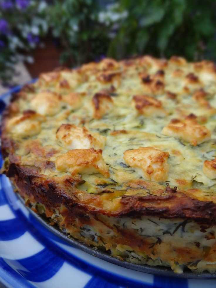 Zucchini Ricotta Savory Cheesecake  2 cups zucchini, unpeeled and coarsely grated 1 tsp fine grain sea salt 2 1/2 cups ricotta cheese 1/2 cup freshly shredded Parmesan cheese 2 shallots, chopped 2 cloves garlic, chopped 1/3 cup fresh dill, chopped zest of one lemon 3 large eggs, well beaten 1/2 cup mozzarella cheese, crumbled drizzle of olive oil