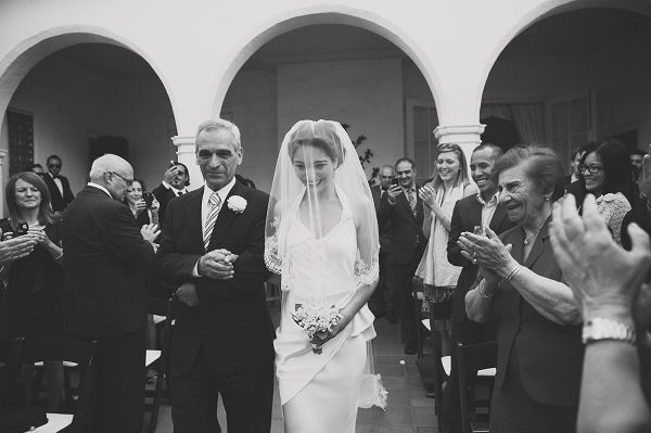 bride walking down the aisle with the tradition of having the veil over her face