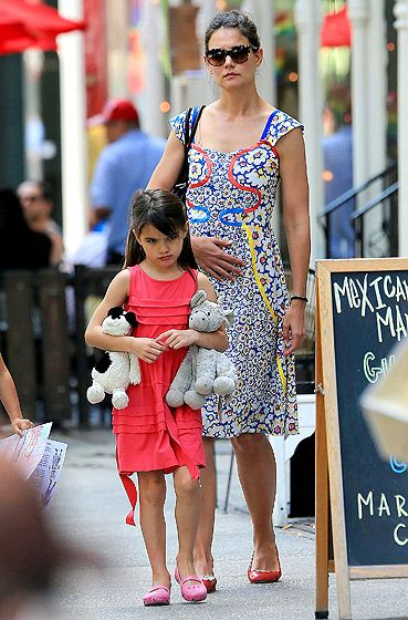 Suri's Pouty Stroll With mom Katie Holmes bringing up the rear, a sulky Suri Cruise (with some dolls) ambled through NYC June 23.