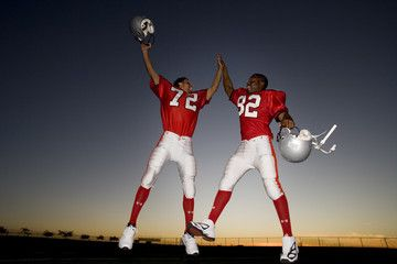 Two American football players celebrating on pitch at sunset, jumping up, doing high-fives, low angle view (backlit)