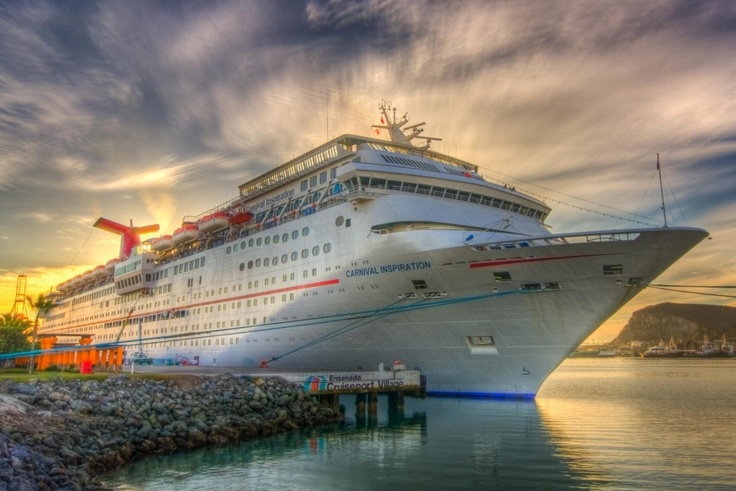 Carnival Inspiration Cruise parked on the clear waters under the blue skies at the port of Mexico