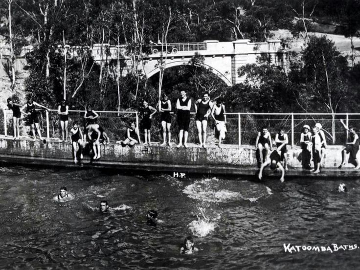 Katoomba Baths  c1920  Katoomba Municipal Baths were opened by the Hon Arthur Griffiths, Minister for Public Works, December 3, 1913. Originally separate pools for ladies and gentlemen, this is the gents pool. The design of R D Fitzgerald was carried out by the Dept of Public Works at a cost of ₤7,600, with Katoomba Municipal Council bearing half the expense. Chelmsford Bridge in the background, with a rather fine open roadster. •Blue Mountains City Library•