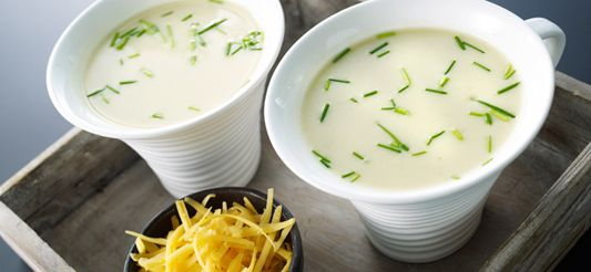 Hak het witloof, de prei en de ui grof. Verwarm de olie in een stoofpot en fruit er de groenten 5 min in op een zacht vuur. Voeg dan de in kleine blokjes gesneden aardappel toe en de nootmuskaat. Meng 1 min., doe er 1 L warm water bij en de verkruimelde bouillonblokjes. Breng aan de kook, dek af en laat 20 min. zacht koken. Rasp de gouda met de grove kant van de rasp. Doe de room en de helft van de gouda bij in de kookpot en mix de soep. Breng op smaak met peper en zout, v...