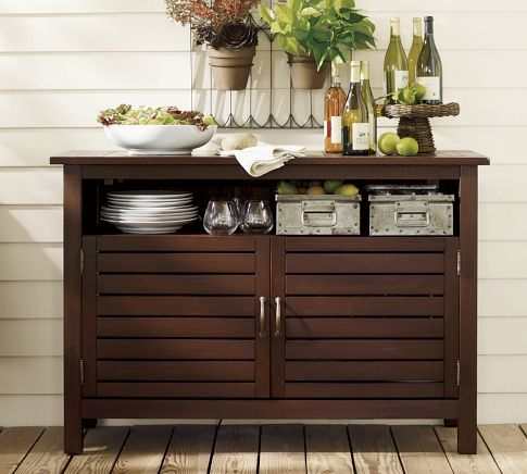 A teak sideboard such as this would be beautiful below the big window.  A great spot to grow potted herbs for the kitchen.  Place a garden sculpture and a candle lantern on top.  It also helps when entertaining to use the sideboard for drinks, etc.