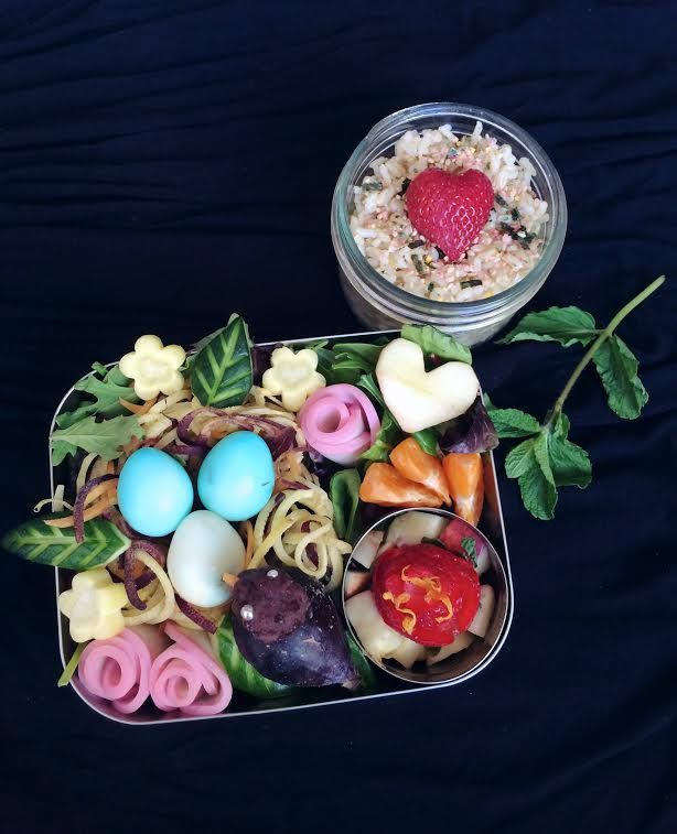 """#92 Mariam Canada This healthier """"sweet tooth"""" bento is blooming with colourful fruits and vegetables. Blue-tinted quail eggs on a nest of veggie noodles, kamaboko flowers, and salad make a tasty meal. For dessert: a robin made from fig and anko, and fruit salad topped with a strawberry rose. Inspired by spring, this bento shows a mother robin watching over her nest and I hope it brings a smile to your face and tummy."""