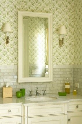 Bathroom with gray marble? subway tile, marble counter, and green geometric wallpaper, with delicate sconces, narrow mirror.