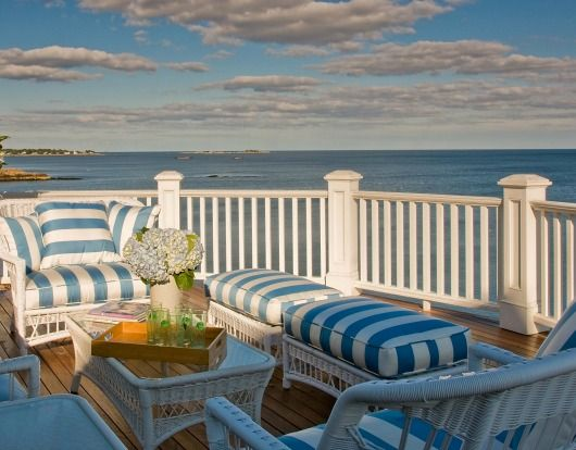 Coastal Porch with White Wicker Furniture and Blue and White Striped Cabana Cushions... http://www.completely-coastal.com/2017/06/white-outdoor-wicker-chairs-loveseat-for-coastal-living.html