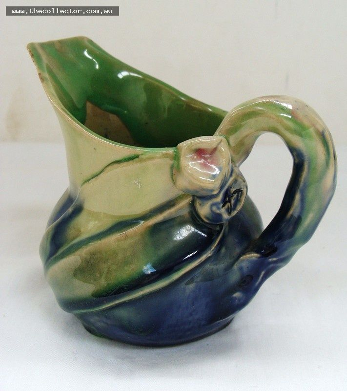 Lot 380 - Remued Australian pottery jug with blue and green glaze with applied gum leaf and gum nuts - marked to base, approx h 95cm