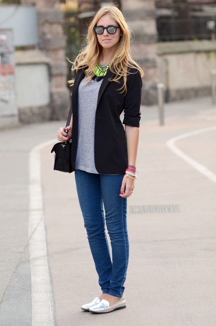 A black blazer, skinny jeans, gray tee, and a funky statement necklace along with metallic loafers creates an easy, casual glam look.