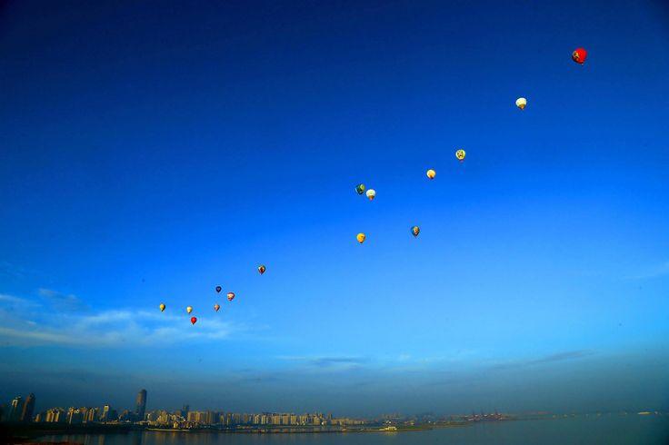15 globos aeroestaticos despegan de la península de Leizhou , en el sur de China, como parte de un concurso llamado China Hot Air Ballon Challenge. (AFP)