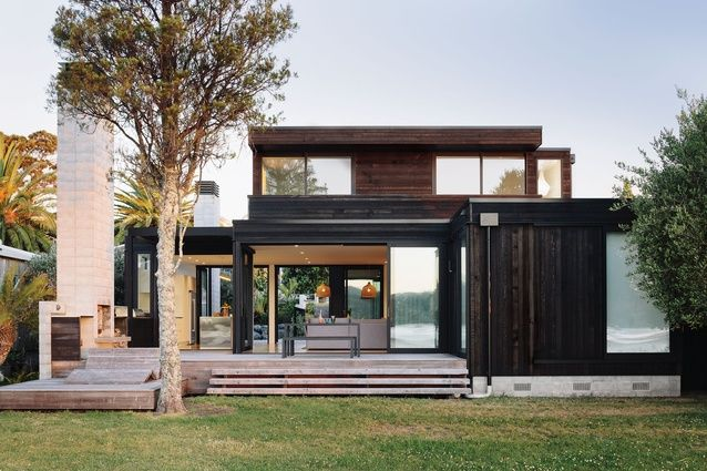 The house is clad with stained cedar and black Colorsteel.