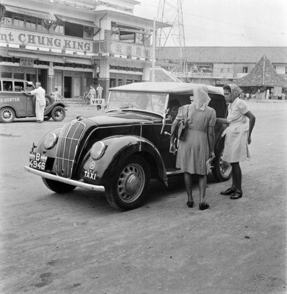 Twee vrouwen staan bij een taxi in Jakarta, Indonesië (1947)