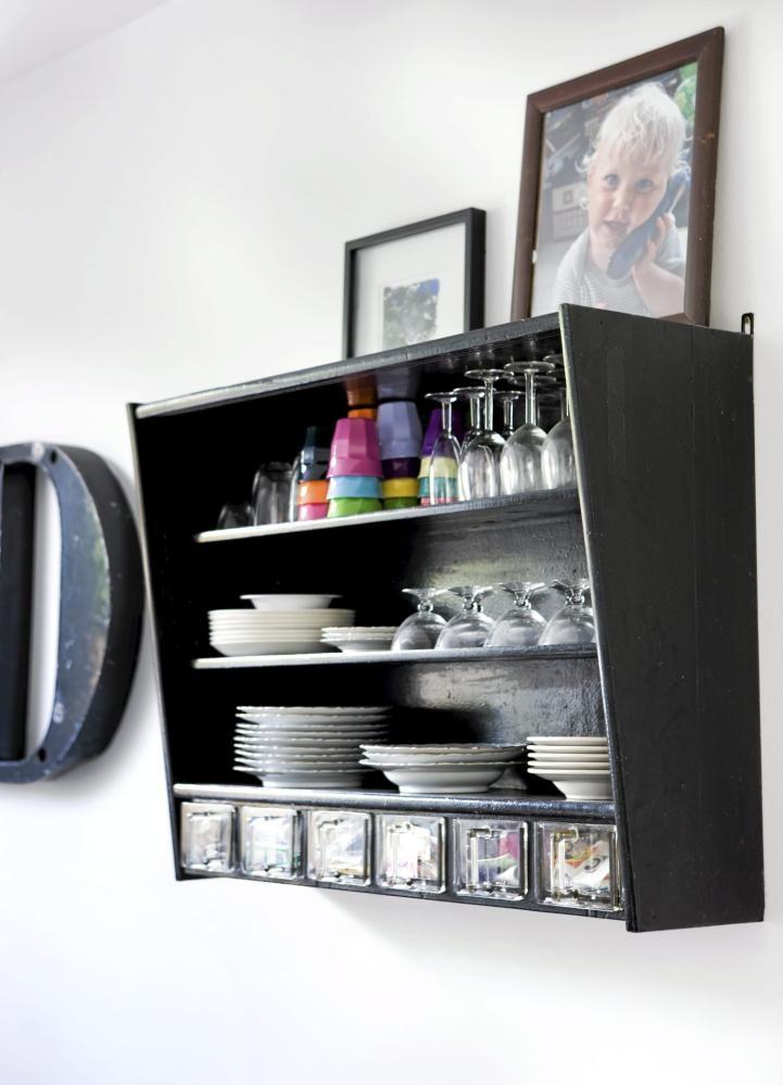 Et gammelt overskap fra kjøkkeninnredningen er malt svart og brukt som hylle i spisestuen. Her har dekkeserviset fått sin plass.