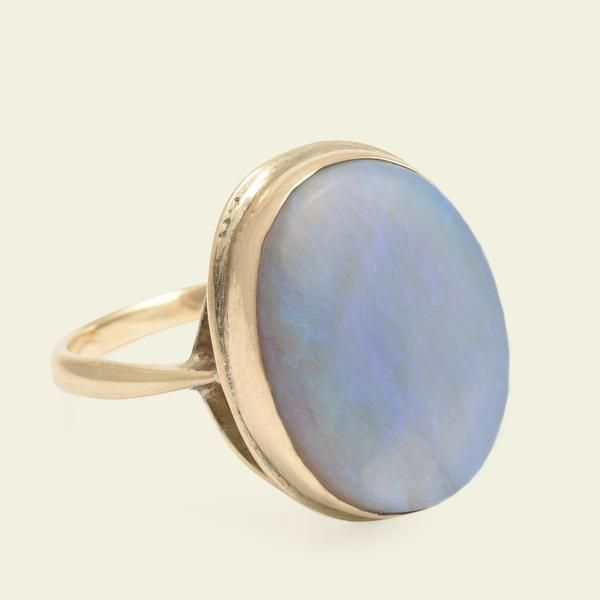 A fabulous example of 1940s excess, this massive cocktail ring is modeled in 9k gold with a big bluish-hued opal cabochon.    Materials: 9k yellow gold, 17.6mm x 13.1mm opal cabochon  Age: c. 1940  Condition: Excellent  Size: US 9.75, can be resized for an additional fee of $90; 2mm hoop  Location: To see this ring in person please visit our shop in Nolita, NYC. ...