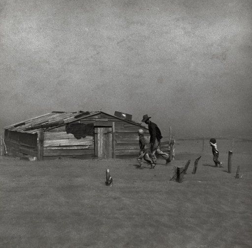 "April 1936. ""Farmer and sons walking in the face of a dust storm. Cimarron County, Oklahoma."" Perhaps Arthur Rothstein's best known Dust Bowl image, and overall one of most memorable photographs to come out of the entire FSA/OWI program. Gelatin silver print by Arthur Rothstein."