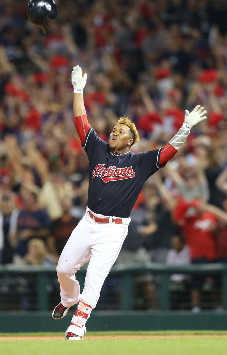 Cleveland Indians Jose Ramirez throws his helmet into the air after knocking in…