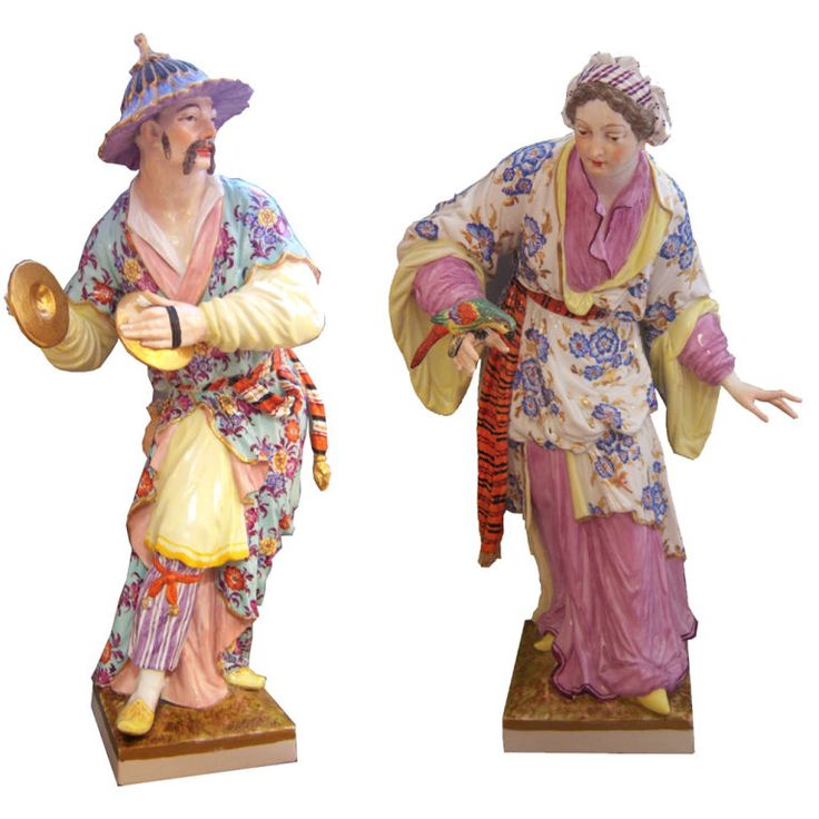Pair of Chinoiserie Figures  Germany  19th Century  Delightful pair of hard paste figurines made in Berlin Germany, Royal Factory, first quarter 19th century. One depicting a musician with symbols, chinoiserie dressed, the other a maiden with a parrot.