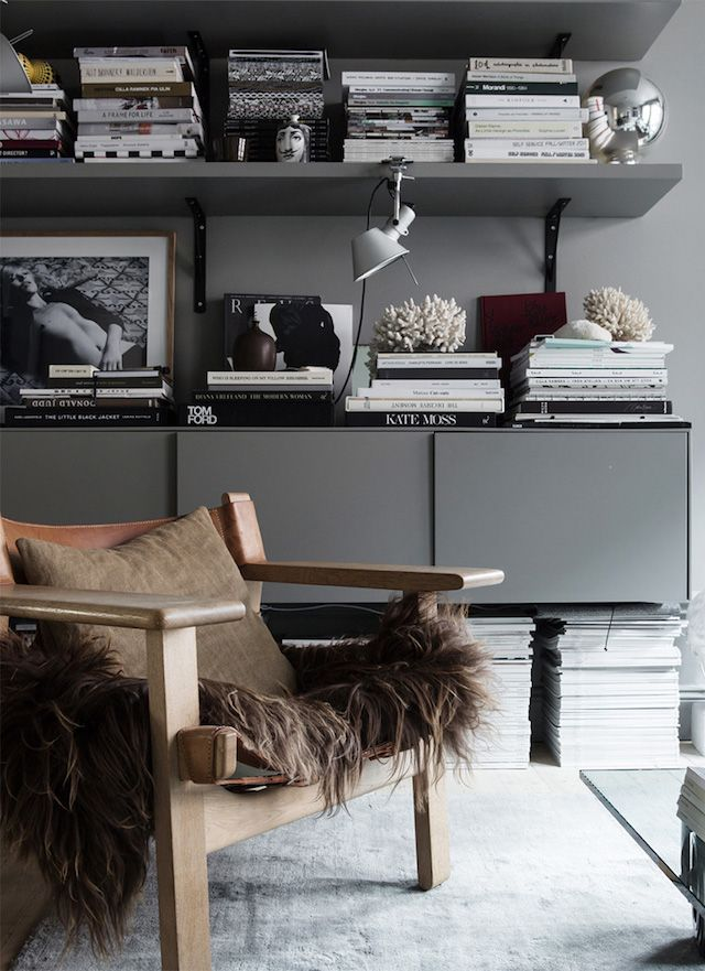 Dark grey shelves and walls and a safari lounge chair in the atmospheric home of Swedish interior designer Lotta Agaton. For sale through ESNY.