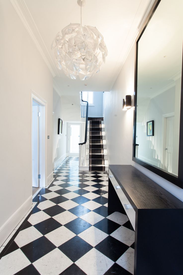 The black and white entrance takes on a minimalist feel with original checkered tiles. A slimline console in dark ebony stained timber is centred along the wall and adorned by an oversized mirror. Black contemporary Flos wall lights flank the mirror and a stunning glass pendant constructed of numerous glass lenses provide al feature for the space.  #blackandwhite #monochrome #hallwayideas #monochromdesign #interiordesign
