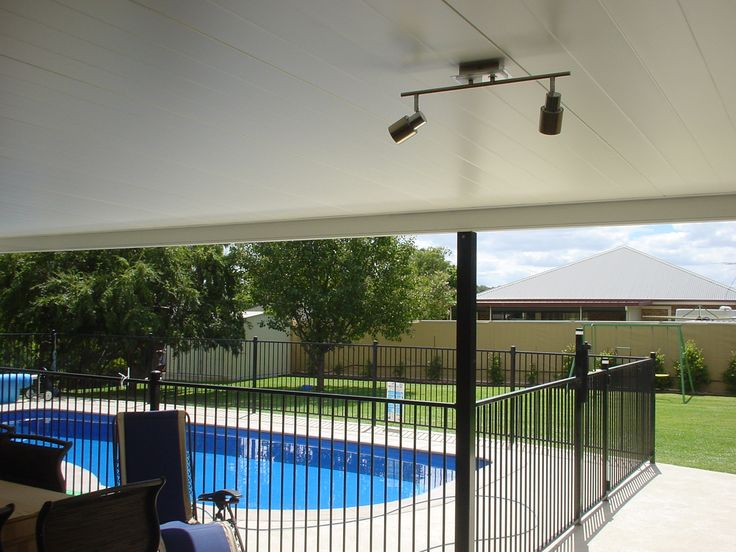 Poolside patio cover with insulated roof panels and lighting fitted.