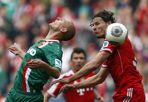 Augsburg's Dominik Reinhardt (L) challenges Bayern Munich's Daniel van Buyten during their German first division Bundesliga soccer match in Augsburg April 5, 2014. REUTERS/Michael Dalder